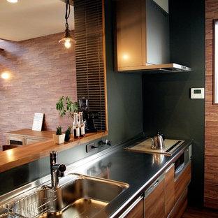 Asiatische Küche mit flächenbündigen Schrankfronten, braunen Schränken, Edelstahl-Arbeitsplatte, Küchenrückwand in Grün, braunem Holzboden und braunem Boden in Sonstige
