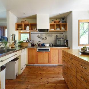 他の地域の広いカントリー風おしゃれなキッチン (一体型シンク、中間色木目調キャビネット、ステンレスカウンター、セラミックタイルのキッチンパネル、黒い調理設備、無垢フローリング、茶色い床、ベージュのキッチンカウンター) の写真
