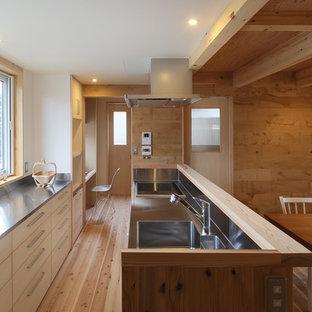 他の地域のおしゃれなキッチン (シングルシンク、フラットパネル扉のキャビネット、淡色木目調キャビネット、ステンレスカウンター、メタリックのキッチンパネル、淡色無垢フローリング、ベージュの床、ベージュのキッチンカウンター) の写真
