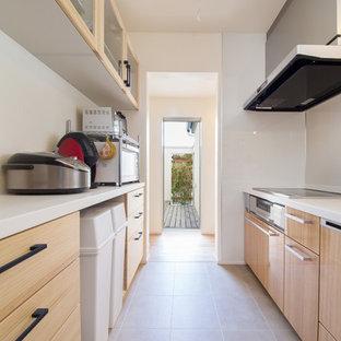 他の地域の北欧スタイルのおしゃれなキッチン (フラットパネル扉のキャビネット、淡色木目調キャビネット、グレーの床) の写真