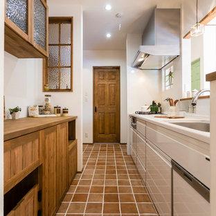 名古屋の地中海スタイルのキッチンの画像 (シングルシンク、落し込みパネル扉のキャビネット、中間色木目調キャビネット、白いキッチンパネル、テラコッタタイルの床、茶色い床)