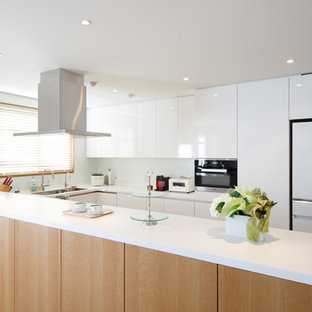 Inspiration for a large modern u-shaped open plan kitchen in Tokyo with a submerged sink, flat-panel cabinets, white cabinets, composite countertops, white splashback, glass sheet splashback, stainless steel appliances, plywood flooring, an island and brown floors.