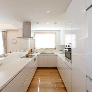 Large modern open concept kitchen ideas - Example of a large minimalist u-shaped plywood floor and brown floor open concept kitchen design in Tokyo with an undermount sink, flat-panel cabinets, white cabinets, solid surface countertops, white backsplash, glass sheet backsplash, stainless steel appliances and an island