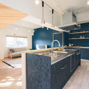 他の地域の北欧スタイルのおしゃれなキッチン (フラットパネル扉のキャビネット、ヴィンテージ仕上げキャビネット、タイルカウンター、淡色無垢フローリング) の写真