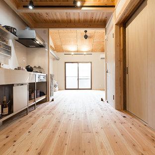 Aménagement d'une cuisine américaine linéaire asiatique avec un évier intégré, un placard sans porte, une façade en inox, un plan de travail en inox, une crédence blanche, un sol en bois brun, aucun îlot et un électroménager noir.