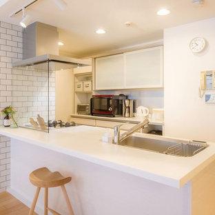 他の地域の北欧スタイルのおしゃれなキッチン (シングルシンク、フラットパネル扉のキャビネット、白いキャビネット、ベージュの床) の写真