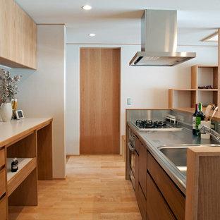 他の地域のアジアンスタイルのおしゃれなII型キッチン (シングルシンク、フラットパネル扉のキャビネット、中間色木目調キャビネット、ベージュキッチンパネル、シルバーの調理設備の、淡色無垢フローリング、ベージュのキッチンカウンター) の写真