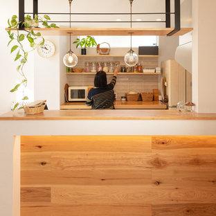 京都のコンテンポラリースタイルのおしゃれなII型キッチン (オープンシェルフ、中間色木目調キャビネット、木材カウンター、グレーのキッチンパネル、無垢フローリング、茶色い床、茶色いキッチンカウンター) の写真