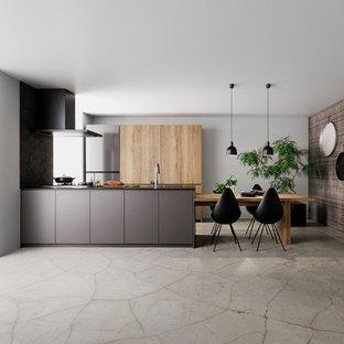 東京23区のモダンスタイルのおしゃれなキッチン (アンダーカウンターシンク、インセット扉のキャビネット、グレーのキャビネット、黒いキッチンパネル、黒い調理設備、コンクリートの床、グレーの床、黒いキッチンカウンター) の写真