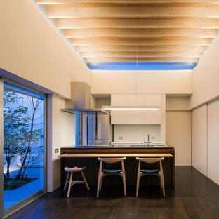 他の地域のモダンスタイルのおしゃれなキッチン (シングルシンク、フラットパネル扉のキャビネット、白いキャビネット、ステンレスカウンター、シルバーの調理設備、濃色無垢フローリング、茶色い床、茶色いキッチンカウンター) の写真