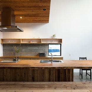 На фото: прямая кухня в восточном стиле с фасадами цвета дерева среднего тона, деревянной столешницей, светлым паркетным полом, островом, обеденным столом и одинарной раковиной с