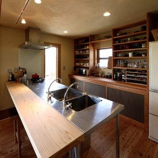 他の地域の和風のおしゃれなキッチン (一体型シンク、オープンシェルフ、黒いキャビネット、ステンレスカウンター、黒いキッチンパネル、木材のキッチンパネル、シルバーの調理設備、無垢フローリング、茶色い床、ベージュのキッチンカウンター) の写真