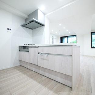 東京23区の北欧スタイルのおしゃれなキッチン (淡色木目調キャビネット、合板フローリング、ベージュの床、白いキッチンカウンター、クロスの天井) の写真