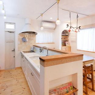 他の地域のアジアンスタイルのおしゃれなキッチン (一体型シンク、落し込みパネル扉のキャビネット、白いキャビネット、白いキッチンパネル、淡色無垢フローリング、茶色い床) の写真