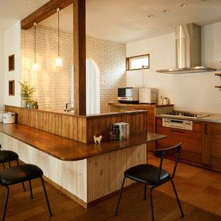 他の地域のアジアンスタイルのおしゃれなキッチン (フラットパネル扉のキャビネット、中間色木目調キャビネット、ステンレスカウンター、白いキッチンパネル、茶色い床) の写真