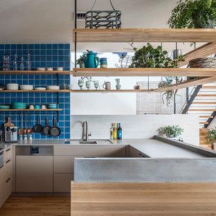 東京23区のモダンスタイルのおしゃれなキッチン (アンダーカウンターシンク、インセット扉のキャビネット、グレーのキャビネット、青いキッチンパネル、黒い調理設備、無垢フローリング、茶色い床、グレーのキッチンカウンター) の写真