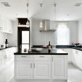 名古屋のトラディショナルスタイルのおしゃれなキッチン (アンダーカウンターシンク、レイズドパネル扉のキャビネット、白いキャビネット、白いキッチンパネル、サブウェイタイルのキッチンパネル、パネルと同色の調理設備、グレーの床、黒いキッチンカウンター) の写真