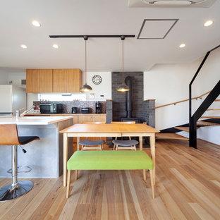 他の地域の広いインダストリアルスタイルのおしゃれなキッチン (茶色い床、白いキッチンカウンター、一体型シンク、淡色無垢フローリング) の写真