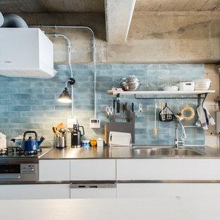 東京23区のコンテンポラリースタイルのおしゃれなキッチン (一体型シンク、フラットパネル扉のキャビネット、白いキャビネット、ステンレスカウンター、青いキッチンパネル、白いキッチンカウンター) の写真