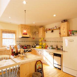 他の地域のヴィクトリアン調のおしゃれなキッチン (淡色木目調キャビネット、タイルカウンター、磁器タイルのキッチンパネル、白い調理設備、ドロップインシンク、淡色無垢フローリング、茶色い床) の写真