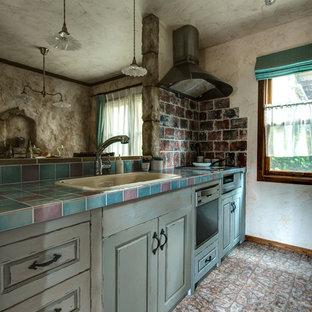 Idée de décoration pour une cuisine linéaire style shabby chic avec un évier posé, un placard avec porte à panneau surélevé, des portes de placard bleues, un plan de travail en carrelage et un sol marron.