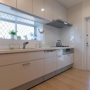 Aménagement d'une petit cuisine américaine linéaire moderne avec des portes de placard blanches, un plan de travail en surface solide, une crédence blanche, un électroménager en acier inoxydable, un sol en contreplaqué, un sol beige, un plan de travail blanc et un plafond en papier peint.