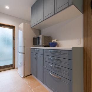 他の地域の小さい北欧スタイルのおしゃれなキッチン (青いキャビネット、人工大理石カウンター、白いキッチンパネル、テラコッタタイルの床、オレンジの床、白いキッチンカウンター、クロスの天井) の写真