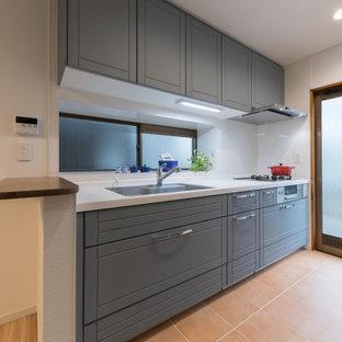 Imagen de cocina lineal, escandinava, pequeña, abierta, con puertas de armario azules, encimera de acrílico, salpicadero blanco, encimeras blancas, suelo de baldosas de terracota, suelo naranja y papel pintado
