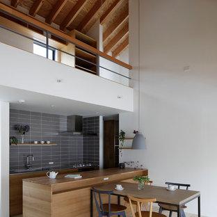 Свежая идея для дизайна: параллельная кухня в восточном стиле с плоскими фасадами, фасадами цвета дерева среднего тона, деревянной столешницей, серым фартуком, светлым паркетным полом, островом, бежевым полом и коричневой столешницей - отличное фото интерьера