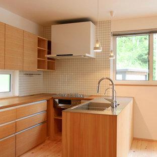 他の地域の大きい和風のおしゃれなキッチン (一体型シンク、インセット扉のキャビネット、中間色木目調キャビネット、ステンレスカウンター、白いキッチンパネル、セラミックタイルのキッチンパネル、白い調理設備、無垢フローリング、白い床) の写真