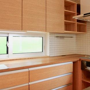 他の地域の広い和風のおしゃれなキッチン (一体型シンク、インセット扉のキャビネット、中間色木目調キャビネット、ステンレスカウンター、白いキッチンパネル、セラミックタイルのキッチンパネル、白い調理設備、無垢フローリング、白い床) の写真