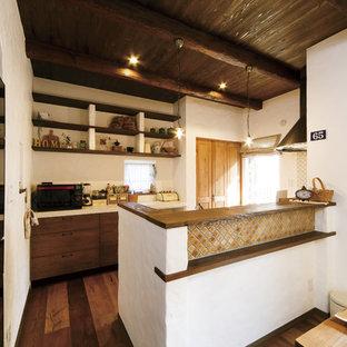 他の地域のアジアンスタイルのおしゃれなペニンシュラキッチン (フラットパネル扉のキャビネット、中間色木目調キャビネット、白いキッチンパネル、濃色無垢フローリング、茶色い床) の写真