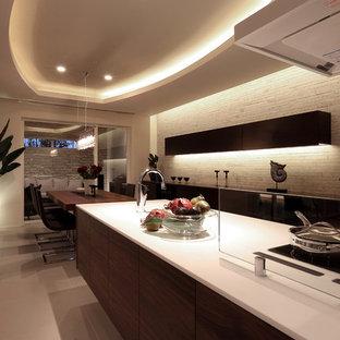 Foto di una grande cucina minimalista con lavello integrato, ante a filo, ante in legno bruno, top alla veneziana, paraspruzzi con lastra di vetro, elettrodomestici neri, pavimento in terracotta, penisola, pavimento bianco e top bianco