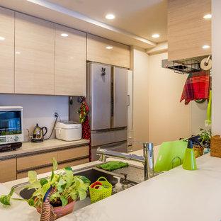 他の地域の中サイズのアジアンスタイルのおしゃれなキッチン (アンダーカウンターシンク、インセット扉のキャビネット、ベージュのキャビネット、人工大理石カウンター、白いキッチンパネル、白い調理設備、合板フローリング、茶色い床) の写真