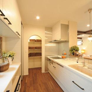他の地域のカントリー風おしゃれなキッチン (白いキャビネット、茶色い床、白いキッチンカウンター) の写真