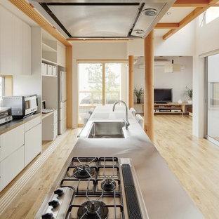 他の地域の大きいモダンスタイルのおしゃれなキッチン (一体型シンク、フラットパネル扉のキャビネット、白いキャビネット、ステンレスカウンター、グレーのキッチンパネル、白い調理設備、淡色無垢フローリング、ベージュの床) の写真