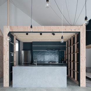 札幌のインダストリアルスタイルのおしゃれなキッチン (一体型シンク、フラットパネル扉のキャビネット、黒いキャビネット、コンクリートカウンター、黒いキッチンパネル、コンクリートの床、グレーの床) の写真