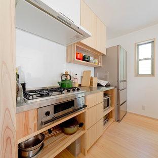 他の地域のアジアンスタイルのおしゃれなII型キッチン (フラットパネル扉のキャビネット、淡色木目調キャビネット、ステンレスカウンター、白いキッチンパネル、淡色無垢フローリング、ベージュの床) の写真