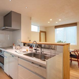 Idée de décoration pour une cuisine américaine linéaire asiatique de taille moyenne avec des portes de placard blanches, un plan de travail en surface solide, une crédence blanche, un électroménager en acier inoxydable, un sol en liège, un sol orange et un plan de travail blanc.