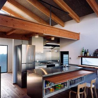 他の地域の中サイズのモダンスタイルのおしゃれなキッチン (一体型シンク、フラットパネル扉のキャビネット、白いキャビネット、ステンレスカウンター、メタリックのキッチンパネル、メタルタイルのキッチンパネル、黒い調理設備、無垢フローリング、赤い床、赤いキッチンカウンター) の写真