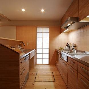 他の地域のモダンスタイルのおしゃれなアイランドキッチン (一体型シンク、中間色木目調キャビネット、ステンレスカウンター、ベージュキッチンパネル、木材のキッチンパネル、シルバーの調理設備の、無垢フローリング、ベージュの床、フラットパネル扉のキャビネット) の写真