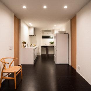 他の地域のコンテンポラリースタイルのおしゃれなキッチン (コルクフローリング、黒い床、シングルシンク、フラットパネル扉のキャビネット、白いキャビネット、白いキッチンパネル、白いキッチンカウンター) の写真