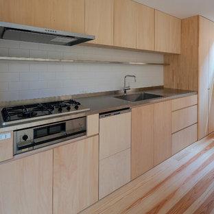 大阪の中サイズのアジアンスタイルのおしゃれなキッチン (一体型シンク、フラットパネル扉のキャビネット、淡色木目調キャビネット、ステンレスカウンター、ベージュキッチンパネル、木材のキッチンパネル、シルバーの調理設備の、塗装フローリング、ベージュの床) の写真