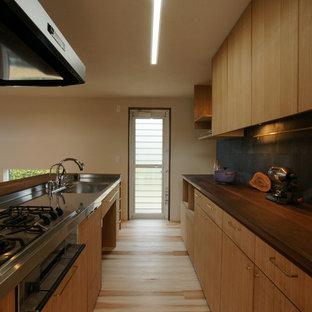 他の地域のアジアンスタイルのおしゃれなキッチン (シングルシンク、フラットパネル扉のキャビネット、中間色木目調キャビネット、淡色無垢フローリング、ベージュの床、茶色いキッチンカウンター) の写真