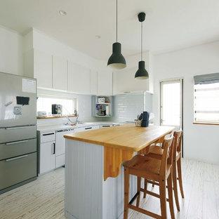 他の地域のビーチスタイルのおしゃれなキッチン (白いキャビネット、白いキッチンパネル、淡色無垢フローリング、白い床、フラットパネル扉のキャビネット) の写真
