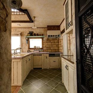 他の地域のシャビーシック調のおしゃれなキッチン (ドロップインシンク、レイズドパネル扉のキャビネット、白いキャビネット、黒い床) の写真