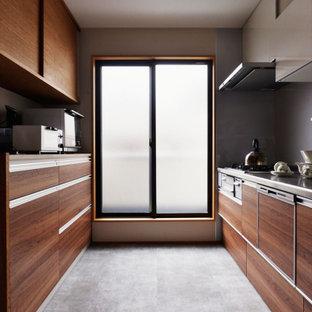 広いコンテンポラリースタイルのおしゃれなII型キッチン (フラットパネル扉のキャビネット、中間色木目調キャビネット、ステンレスカウンター、グレーのキッチンパネル、磁器タイルのキッチンパネル、パネルと同色の調理設備、磁器タイルの床、グレーの床、グレーのキッチンカウンター) の写真