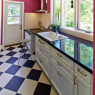他の地域のトラディショナルスタイルのおしゃれなキッチン (白いキャビネット、大理石カウンター、マルチカラーの床、シングルシンク、白いキッチンパネル) の写真