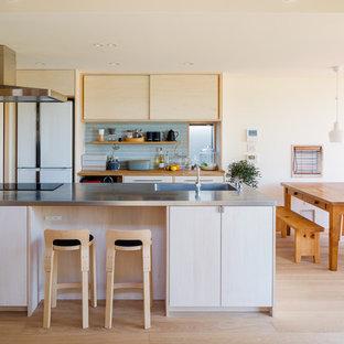他の地域のコンテンポラリースタイルのおしゃれなキッチン (一体型シンク、フラットパネル扉のキャビネット、淡色木目調キャビネット、ステンレスカウンター、青いキッチンパネル、白い調理設備、淡色無垢フローリング、ベージュの床) の写真