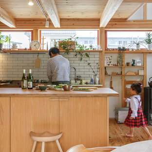 他の地域のアジアンスタイルのおしゃれなキッチン (フラットパネル扉のキャビネット、淡色木目調キャビネット、木材カウンター、白いキッチンパネル、シルバーの調理設備の、無垢フローリング、茶色い床、茶色いキッチンカウンター) の写真